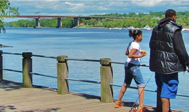 Man and daughter fishing from pier overlooking the Hudson River